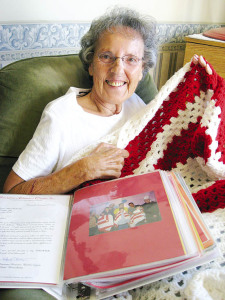 Alma Dalinsky, a resident of St. Anne's Retirement Community, displays one of her handmade afghan blankets and a scrapbook full of thank you cards and letters. Dalinsky has crocheted more than 133 afghans.